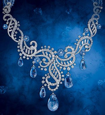 Cartier's high jewelry sapphire series necklace. It is made of platinum, diamonds, and sapphires. There are seven oval-shaped incised sapphires dropping below diamonds and platinum is curved into hollow patterns. They inlay with each other and the oblong diamonds in the hollow area.