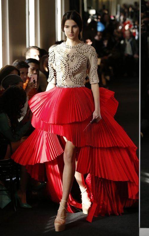 Stephane Rolland - Le public a découvert de nombreuses créations asymétriques. Courtes devant, elles dévoilent de longues traînes à l'arrière, pour un glamour survolté. Stephane Rolland maîtrise l'exercice comme le montre sa robe rouge et crème, dont le corset sculpté est associé à une jupe à volants plissés. - Haute couture : entre mode et oeuvres architecturales - Actualité : Défilés (#622941)