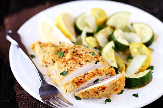 Hummus Crusted Chicken  4 boneless, skinless chicken breasts  salt and pepper  1 zucchini, chopped  1 yellow squash, chopped  1 medium onion, chopped  1 cup hummus, homemade or storebought  1 Tbsp. olive oil  2 lemons  1 tsp. smoked paprika or sumac