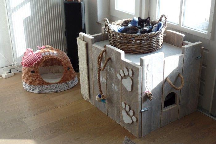 Een gezellig kattenhuis in de woonkamer. Gemaakt van vergrijsde steigerplanken. Binnenin staat de kattenbak.