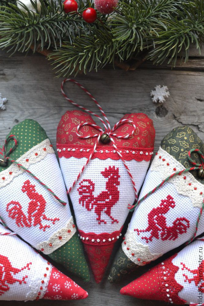 Хочу показать вам небольшой мастер-класс по созданию новогоднего сердечка с петушком — символом 2017 года. Размер готового сердечка 9х15 см. Итак, нам понадобится: - новогодняя ткань хлопок; - петушок, вышитый крестиком (канва, нитки мулине); - кружево; - наполнитель синтепух или холлофайбер; - декоративный шнур; - бубенчик; - бисер; - нитки; А также: - ножницы; - иголки; - палочка для набивания; - машинка швейная (но можно обойтись и без нее).