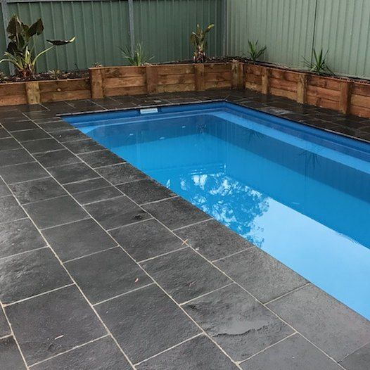 Amber Tiles Kellyville: Rich and natural licorice limestone by @ambertiles. Bullnosed coping to suit this family pool by Custom Pools #limestone #poolsurround #poolinspiration #naturalstone #ambertiles
