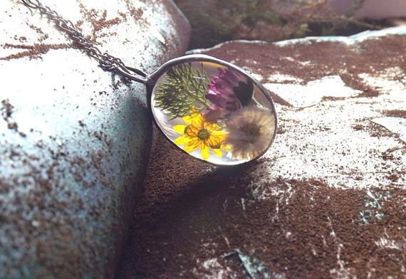 Pendant with daisy yellow flower and field plant. Real flower