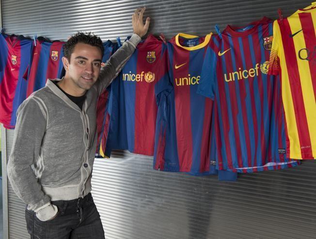 Xavi Hernández, posando con varias camisetas del Barça que ha vestido a lo largo de su trayectoria.