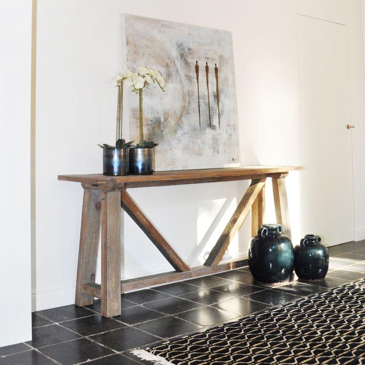 Je kan makkelijk de aandacht naar een kunstwerk of schilderij brengen door dit op een houten tafel te plaatsen. Doordat het hout neutraal is, leidt dit niet af. Maak het geheel af door te werken met trendy accessoires.
