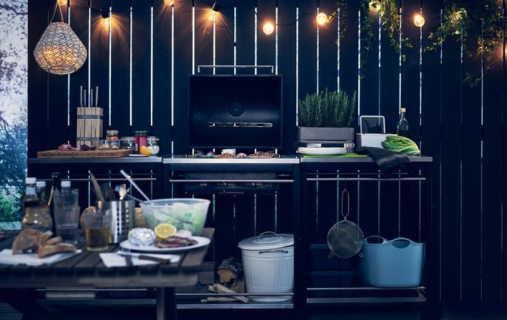 Ei lyslenke henger over et utendørskjøkken i tre deler, inkludert en grill, som står mot et svart tregjerde.