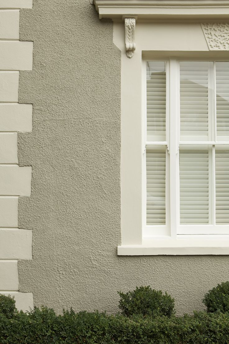 House painted in Farrow  Ball Masonry Paint - Light Gray rendering with bricks and window surround in Off-White and wooden window frame in Wimborne White Exterior Eggshell.