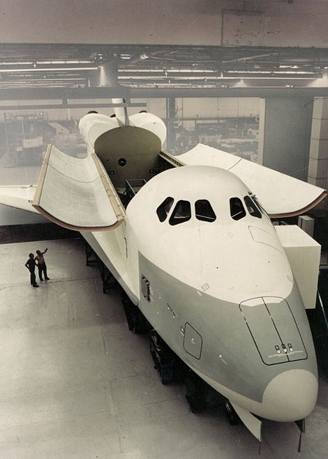 """February 27, 1975 — Employees at Rockwell International Corporations Space Division, Downey, California, look over a full-scale mockup of the Space Shuttle orbiter."""