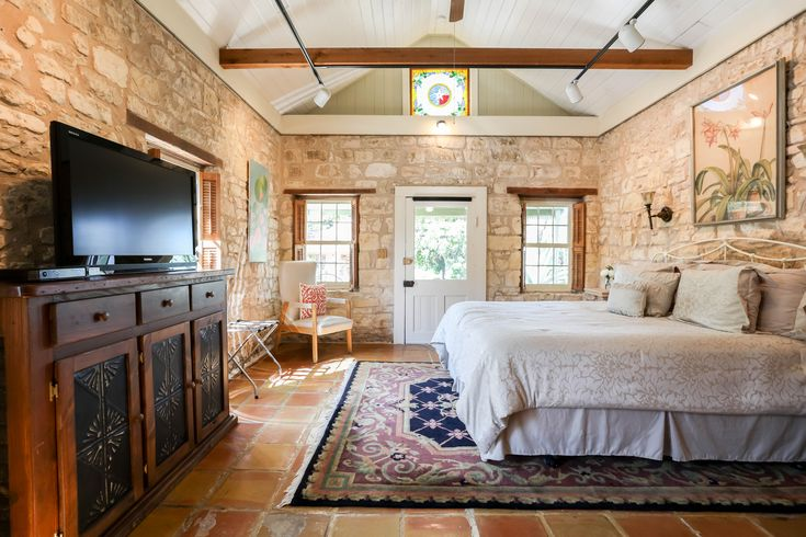 A fantastic king bed surrounded by majestic limestone walls insures that Agave Sunday House's bedroom is a truly amazing space. #fredericksburg #texas #fbgtx #stone #limestone #wall #bedroom #beautiful #home #fbglodging
