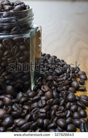 Coffee beans in transparent jar and on wooden table. High resolution image.