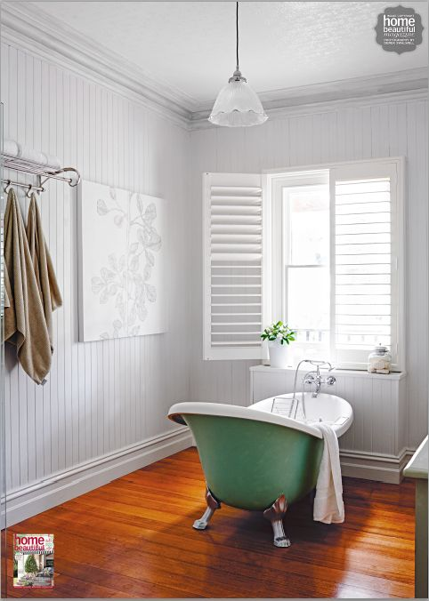 This green freestanding bathtub makes an elegant and unique focal point of the room. Like the shutters.