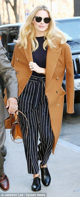 Cool in camel: The Australian actress teamed the classic wardrobe staple with blue and white striped trousers which were cropped just above the ankle and finished on the waist