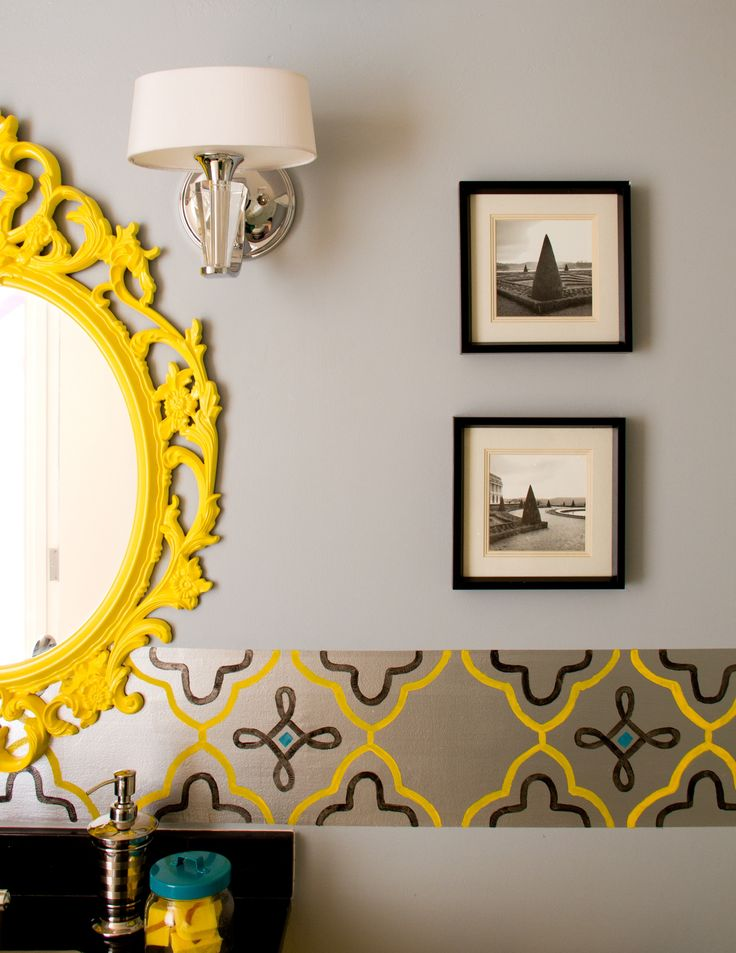 A Hollywood Regency bathroom featuring thassos floor tiles, toto fixtures, frameless shower glass, and a hand painted wall border.  The Yellow mirror makes it special.  Credits: The Property Sisters  Designer: Marilynn Taylor, TheTayloredHome.com Co-Designer: @allandallatore Contractor: Allison Allain, PlumbCrazyContracting.com