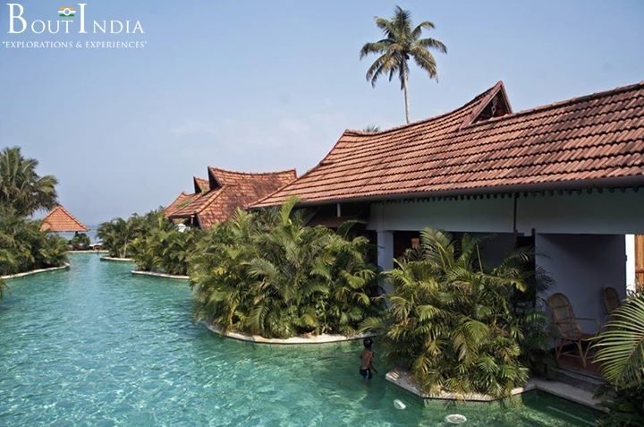 A large swimming pool between holiday chalets in the backwaters of Kumarakom, Kerala - The Venice of India. Kumarakom is a small village and a popular backwater tourist destination located near the city of Kottayam in Kerala state. It is a cluster of small islands on the Vembanad Lake which is one of the largest backwaters lakes in the state of Kerala.  #Kumarakom #India #backwaters #village #Kottayam #Kerala #VembanadLake