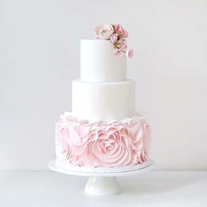 Beautiful traditional white wedding cake with pink details