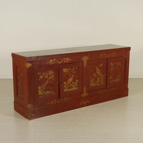 Credenza retta da zoccolatura, presenta quattro ante. Laccata con decorazioni chinoiserie.