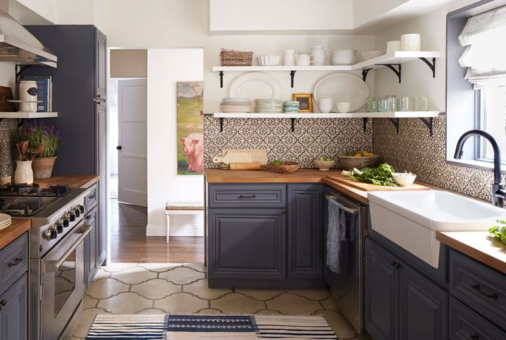 As an homage to the home's architectural roots, Emily clad the backsplash in black-and-white Spanish tiles. The graphic colorway puts a fresh, modern twist on the old-fashioned arabesque motif. Large-scale concrete floor tiles echo the curvy shape of the backsplash tile for a cohesive feel. From there, Emily transformed the cabinets with a few coats of paint in deep periwinkle, one of Shana's favorite colors. The butcher-block countertops were a warm, low-cost alternative to marble or…
