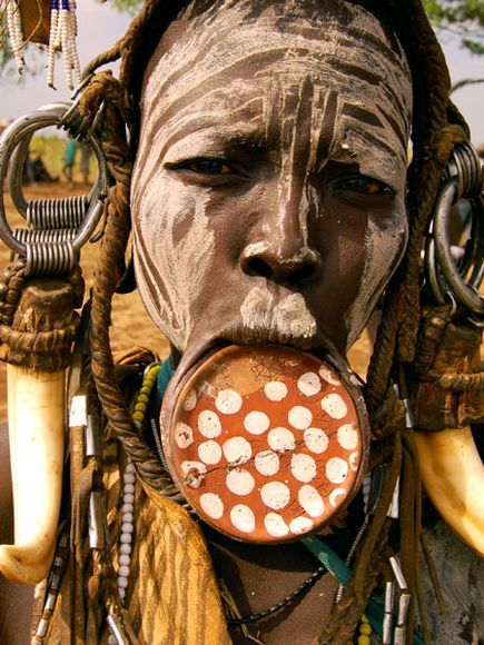A Mursi woman from the Omo Valley in southern Ethiopia is adorned with face markings and an ornamental clay lip plate, considered signs of beauty among her people.