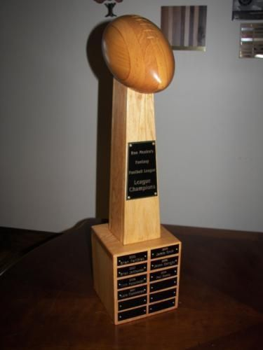 "Wood Fantasy Football Trophy is a hand crafted Custom Award 28"" tall x 7"" wide with12 plates per side for annual winners. Engraving of league name on header plate included. These quality trophies are hand made in Milwaukee, so plan on 4 week lead time. Wood Fantasy Football Trophy is at www.rcbawards.com."