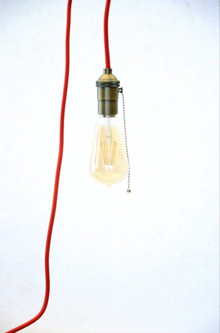 Restauramos una roldana antigua de hierro para darle un segundo uso, una lámpara. Tiene cable de tela color rojo y un portalámpara metálico antiguo.