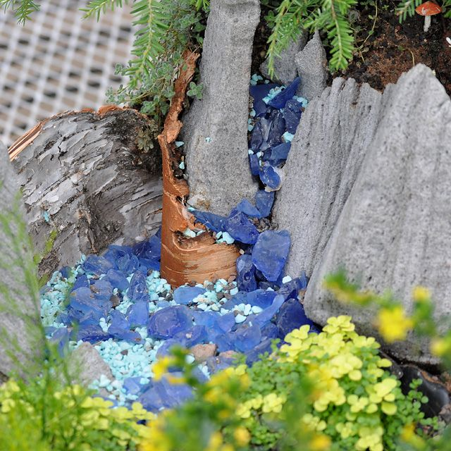 Stone waterfall to create a waterfall place blue glass for Garden mini pool