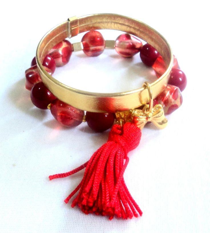 Cód: PUL501 <br> <br>Conjunto com 2 pulseiras em couro sintético liso dourado, bolas acrílicas vermelhas, franja tassel vermelha e pingente de laço.