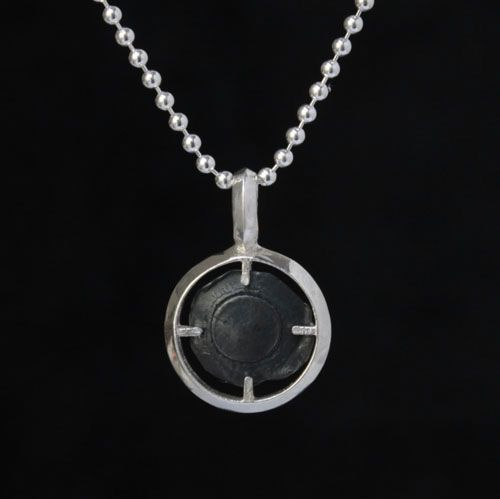 A finely polished sterling silver frame, with blackened sterling silver bullet. This finely crafted pendant comes with sterling silver chain or rubber necklace in 16,18, or 20 inch length. Size is Marksman. First Edition.