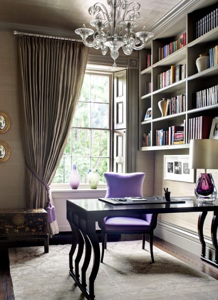 The full curtains, upholstered chair and chandelier give this home office a sense of opulence