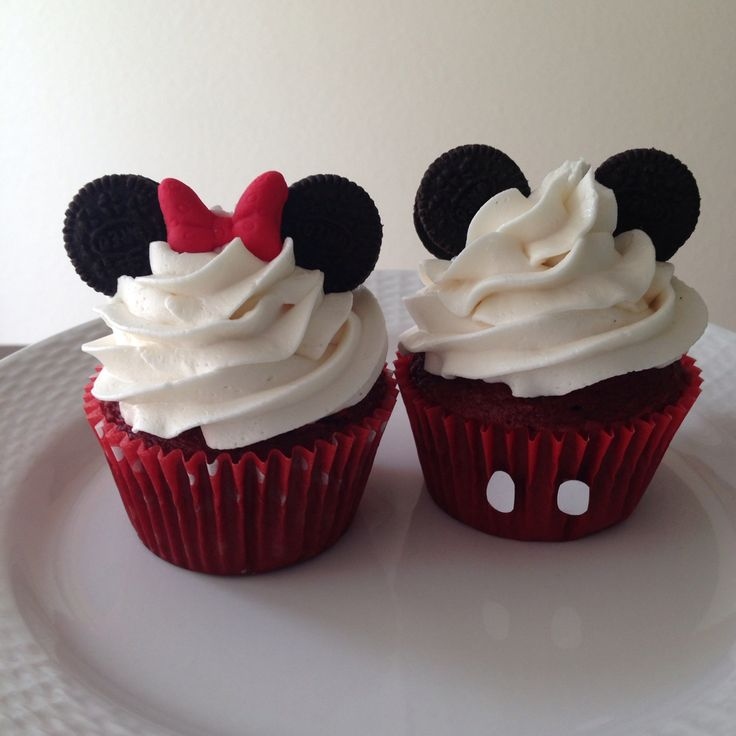Mickey and Minnie Mouse cupcakes with mini Oreo ears. Red velvet cake in red and red with white polka dot liners. Vanilla buttercream. Red fondant Minnie bow. Made by Play Date Cupcakes in Hawaii.