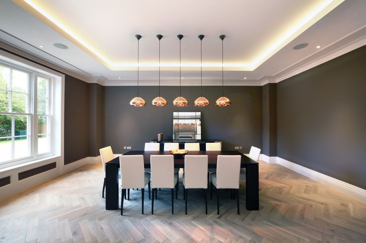 LED ribbon in this coffered ceiling help break up what would be an otherwise large area of flat ceiling.  A row on pendants make a feature of the dining table.