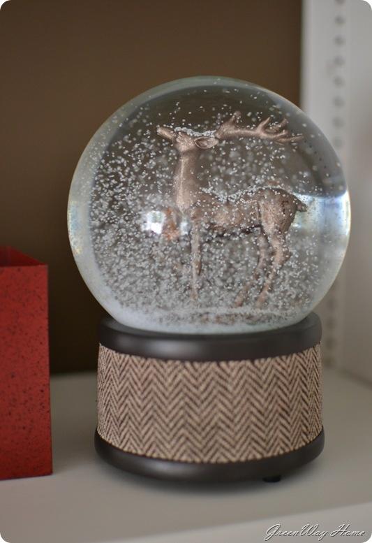 Deer snow globe with herringbone wool on a wood base.