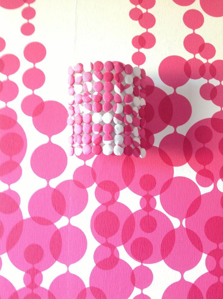 Aplic fet amb botons folrats amb el mateix paper de la paret