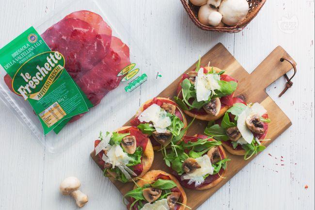 La schiacciatina con bresaola e rucola, con l'aggiunta di funghi e scaglie di grana è un finger food rustico e appetitoso per un aperitivo informale!