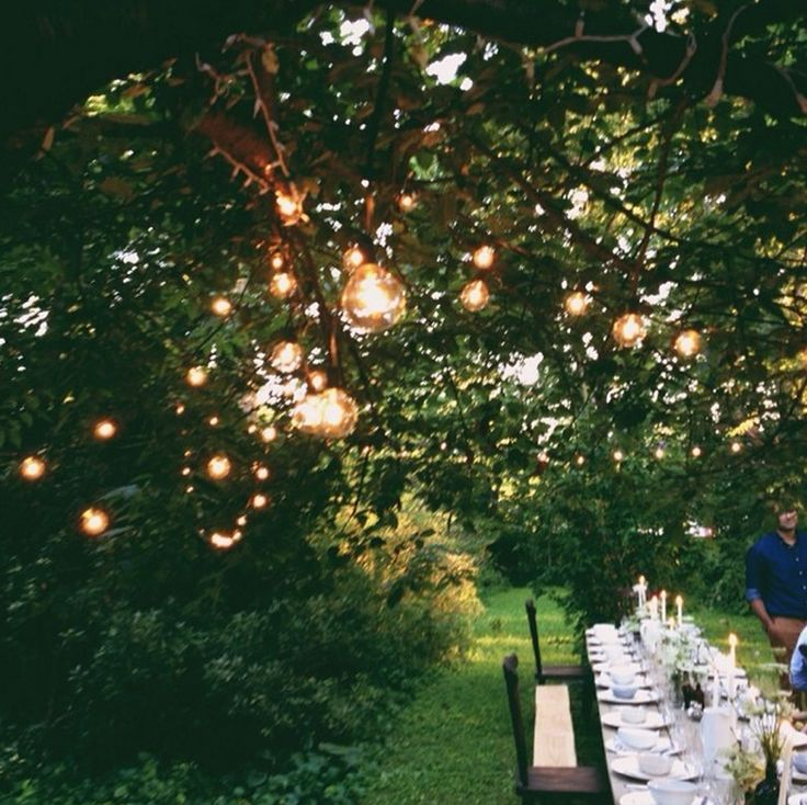 Globe lights in trees, long reception tables at sunset - perfect backdrop to an outdoor wedding reception {repinned by theheartstate.com}