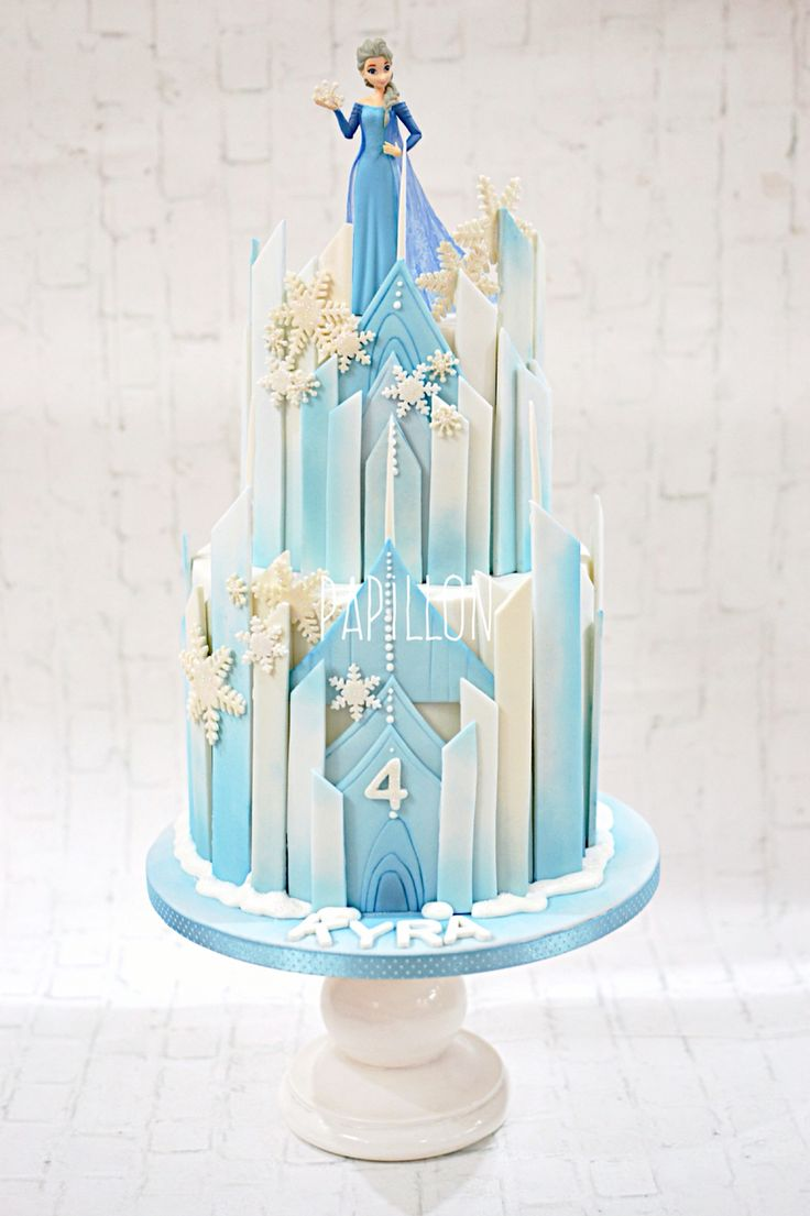 Frozen themed castle cake with Elsa toy figure More