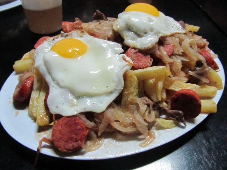 Chorrillana: Nacida en el puerto de Valparaíso, un plato a base de papa, cebolla cortada muy fina, longaniza, bistec y de coronación uno o dos huevos fritos. #PlatosDeChile #ChileanDishes