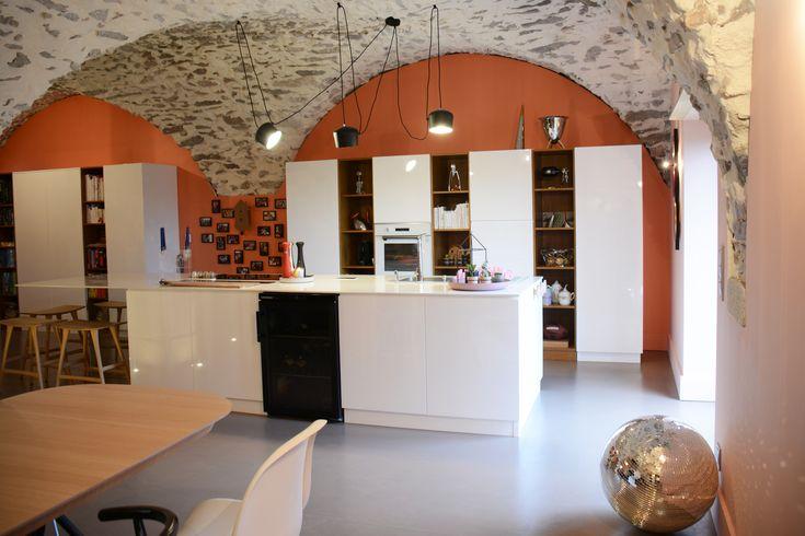 Grande cuisine blanche avec pierres apparentes : au sol béton ciré sur fond orange.