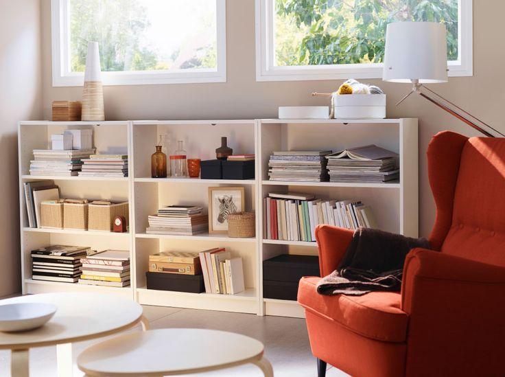 背の低いホワイトのBILLY/ビリー 書棚を3台並べて、その前にオレンジのSTRANDMON/ストラドモン ウィングチェアを置いた半地下のリビングルーム