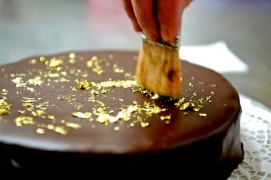 Decorating a chocolate cake with gold leaf This is what we shall have