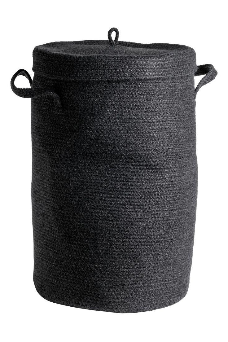 Sort. En skittentøykurv i flettet jute. Skittentøykurven har lokk med håndtak øverst og håndtak i sidene. Diameter 34 cm. Høyde uten lokk 52 cm.