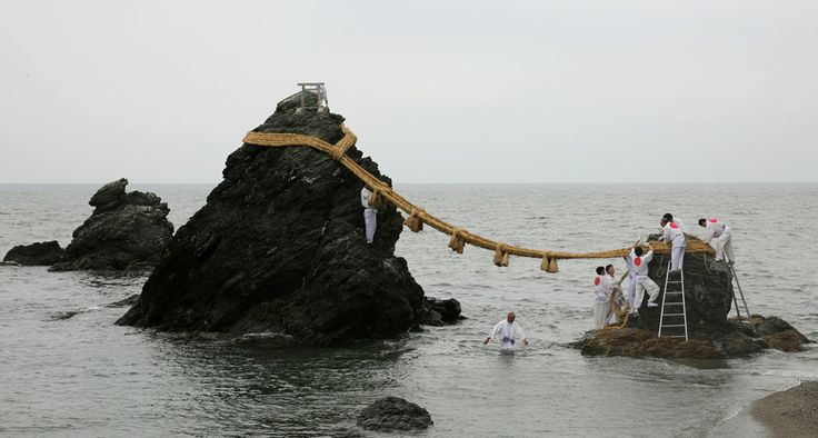 """""""Japanese Shinto shrine priests hang the Shimenawa, Sacred ropes strung between God Married Stones, during the Oshimenawahari ceremony of Meoto-iwa or the Couple Rock at Futami Okitama Shrine in in Ise, Japan. The Oshimenawahari ceremony is held three times a year to replace the heavy rope of rice straw that connects the Couple Rock. The Rock serves as a gate to the Okitama Shrine, dedicated to the god Sarutahiko and goddess Ukanomitama from Japanese myth. (Buddhika Weerasinghe/Getty Images)"""
