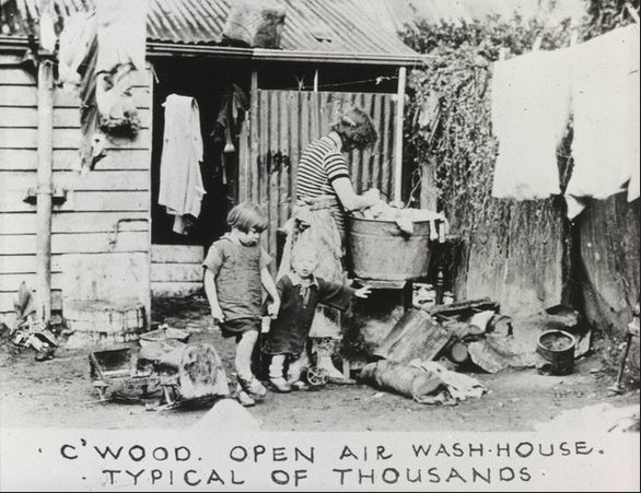 Open air wash house, Melbourne. This woman is standing at a copper washing clothes. This photo is in the F. Oswald Barnett Collection, taken in the 1930s. Many of them were used to illustrate a government report on slum housing and/or made into lantern slides for lectures in a public campaign.