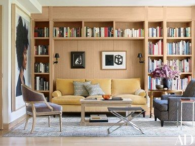 Neal Beckstedt Studio designed the interiors, furnishing the library with a Roman Thomas sofa, a Christian Liaigre club chair, and a vintage André Arbus cocktail table and Poul Kjærholm stool; the large artwork is by Chuck Close, and the black-framed piece above the sofa is by Kara Walker   archdigest.com