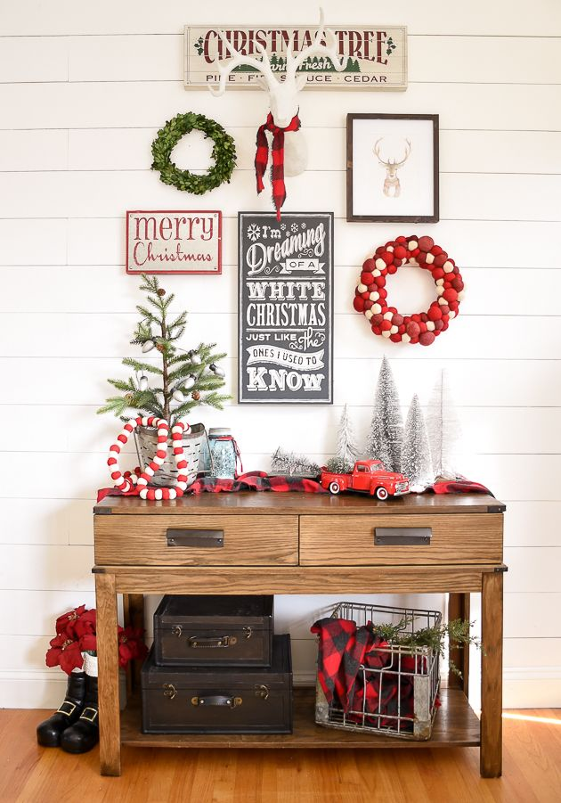 A beautiful and classic Christmas entryway and living room featuring shades of red, green and black. #christmas #holidaydecor #gallerywall #christmasentryway