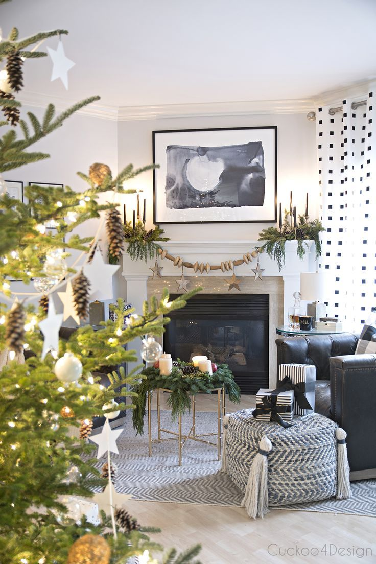 Modern European Eclectic Christmas Tree with pinecones, white stars, clear Christmas balls and white Christmas balls on a real untrimmed fir tree   blue, white and black fireplace area with leather swivel chairs