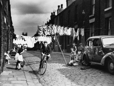 © Shirley Baker  Cycling Along a Terraced Street - Salford, Manchester 1962