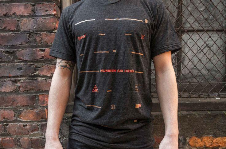 Bedrukking van T-shirt. Simpel en niet te druk. Er is gebruik gemaakt van rode en gouden lijntjes. Hier en daar een symbool of vermelding van het merk.