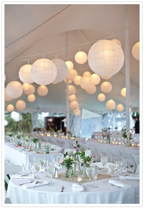 Elegant white paper lanterns in the tent of the wedding reception…