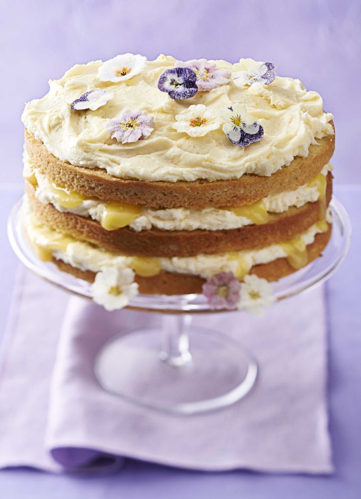 Lemon curd layer cake: A showstopping, lemony sponge cake with a delicious curd icing and beautiful edible crystallised violets and primroses from eatmyflowers.co.uk.