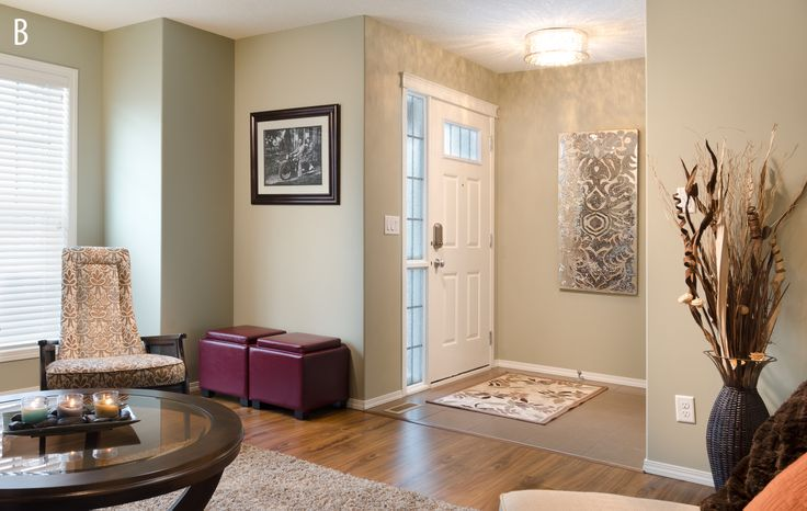 Private residence by Morrison Homes - Winner of a 2013 #SAMCalgary Award, light olive walls, stone artwork and hardwood floors make this foyer an inviting entrance to all